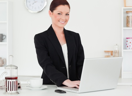 Pretty red-haired woman in suit relaxing with her laptop while posing in the kitchen in her appartment photo