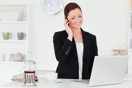 Pretty red-haired woman in suit relaxing with her laptop while phoning in the kitchen in her appartment photo