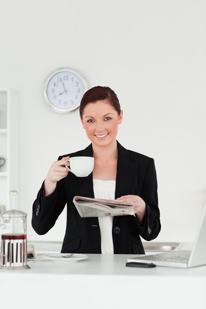 Attractive red-haired woman in suit reading the newspaper while having her breakfast in the kitchen in her appartment photo