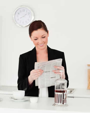 Good looking red-haired woman in suit reading the newspaper in the kitchen in her appartment photo