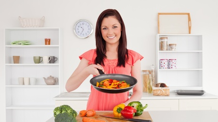 Beautiful red-haired woman cooking vegetables in the kitchen in her appartment photo