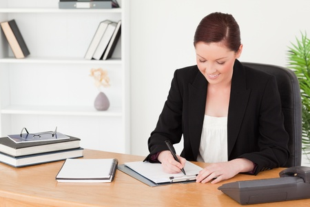 Beautiful red-haired woman in suit writing on a notepad while sitting in an office photo