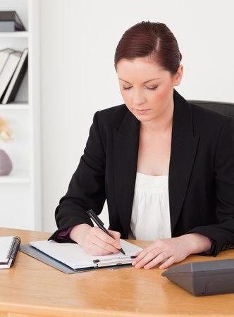 Gorgeous red-haired woman in suit writing on a notepad while sitting in an office photo