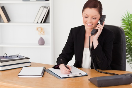 Beautiful red-haired woman in suit writing on a notepad and phoning while sitting in an office photo