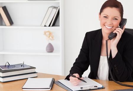 Pretty red-haired woman in suit writing on a notepad and phoning while sitting in an office photo