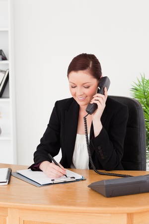 Young attractive red-haired woman in suit writing on a notepad and phoning while sitting in an office photo