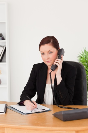 Young gorgeous red-haired woman in suit writing on a notepad and phoning while sitting in an office photo