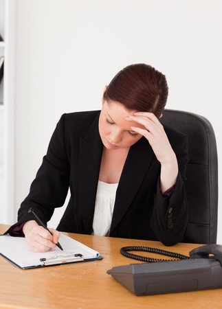 Depressed beautiful red-haired woman in suit writing on a notepad while sitting in an office photo