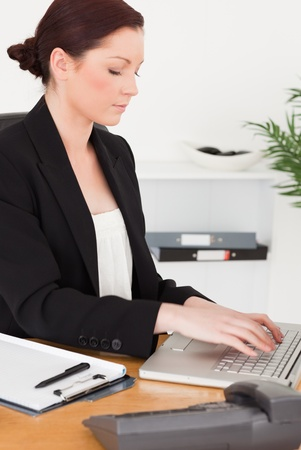 Young attractive red-haired woman in suit typing on her laptop while sitting in an office photo