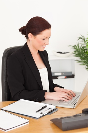 Young beautiful red-haired woman in suit typing on her laptop while sitting in an office photo