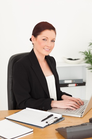 Young attractive red-haired woman in suit typing on her laptop and posing while sitting in an office photo