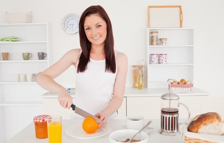 Young attractive red-haired woman cutting an orange in the kitchen in her appartment photo