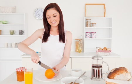 Young beautiful red-haired woman cutting an orange in the kitchen in her appartment photo