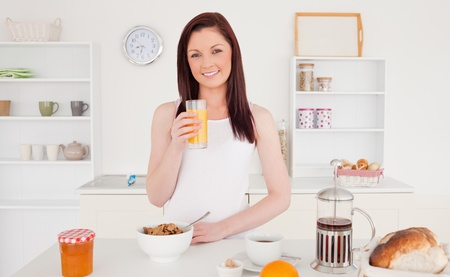 Young pretty red-haired woman drinking a glass of orange juice in the kitchen in her appartment photo