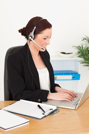 Young attractive red-haired woman in suit typing on her laptop and using headphones while sitting in an office Stock Photo - 10071270
