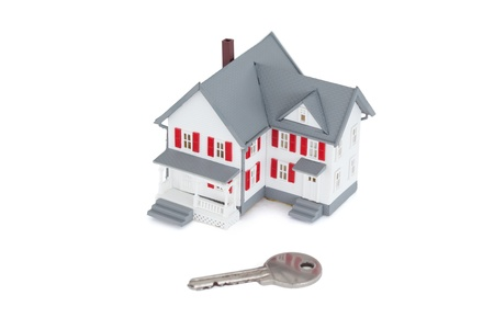 Miniature house with a key against a white background photo