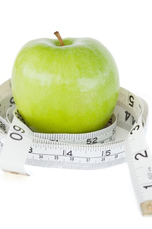 Closeup of a green apple circled with a tape measure against a white background photo