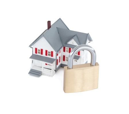 Concept images of a miniature grey house with a padlock against a white background photo