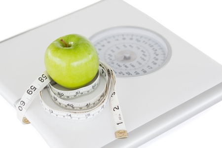 Green apple circled with a tape measure and weigh-scale against a white background photo