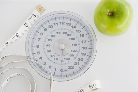 dietetical: Top view of a green apple along with a tape measure and a weigh-scale against a white background Stock Photo