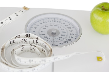 Green apple with a tape measure and a weigh-scale against a white background photo
