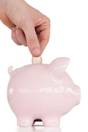 Hand inserting a coin in a pink piggy bank against a white background.  photo