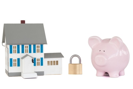 House locked with padlock and pink piggy bank against a white background  photo
