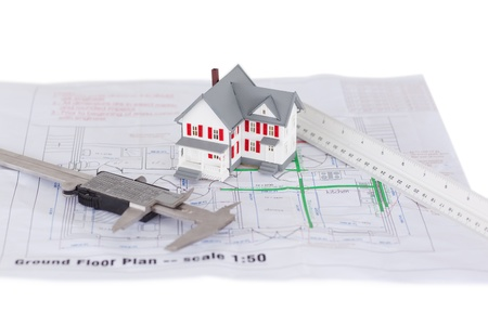 Toy house model and ruler and on a plan against a white background photo