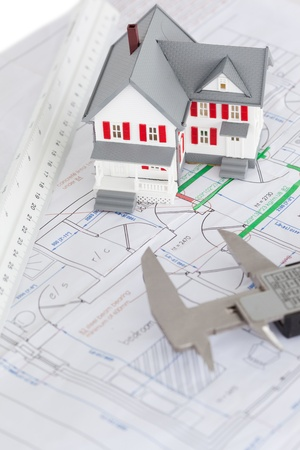 Top view of toy house model and caliper on a plan against a white background Stock Photo - 10073218