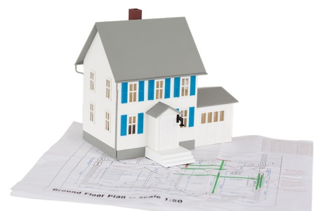 Gray toy house model on a ground floor plan against a white background photo