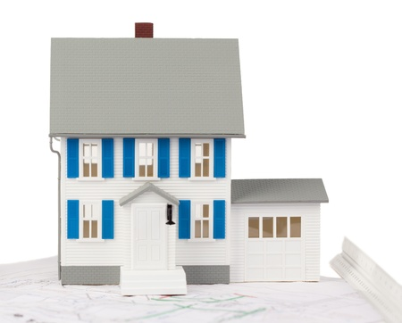 Front view of a toy house model on a ground floor plan against a white background photo