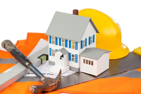 Tools and miniature house on an orange jacket against a white background Stock Photo - 10071900