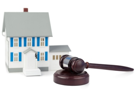 Grey toy house model and brown gavel against a white background photo