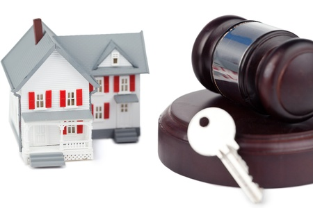 Closeup of a toy house model and a brown gavel against a white background Stock Photo - 10070850