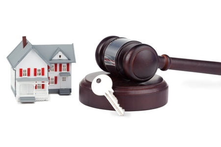 Closeup of a toy house model and a brown gavel against a white background Stock Photo - 10069610
