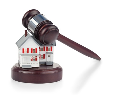Closeup of a toy house model and a brown gavel against a white background Stock Photo - 10069665
