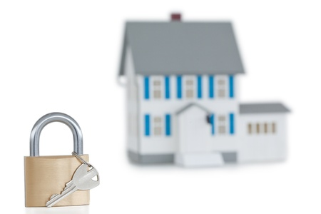 Miniature house and opened padlock against a white background Stock Photo - 10069677