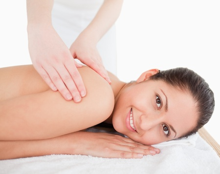brunette having shoulder massage in a spa photo