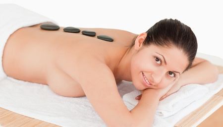 brunette having a black stone massage in a spa photo