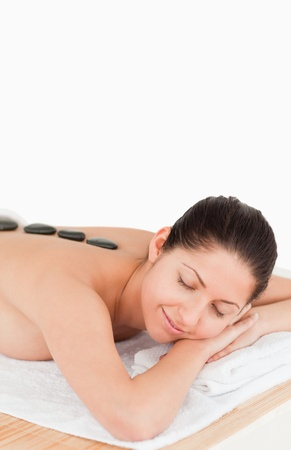young dark-haired woman having a stone massage eyes closed Stock Photo - 10069754