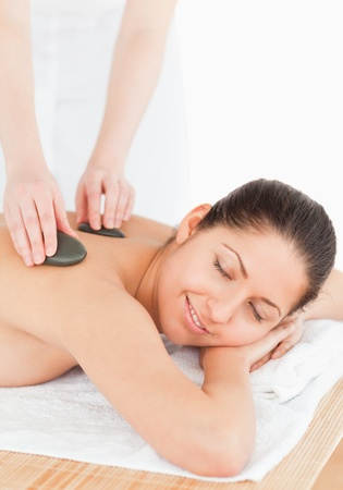 smilling brunette relaxing while having a stone massage eyes closed Stock Photo - 10070123