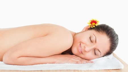 young woman lying on a massage table and a flower on her ear in a spa photo