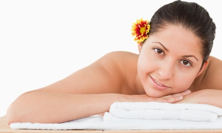young woman in a spa with a flower on her ear on a massage table photo