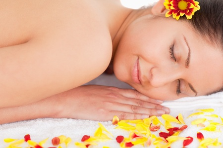 dark-haired woman surrounded by flowers sleeping photo