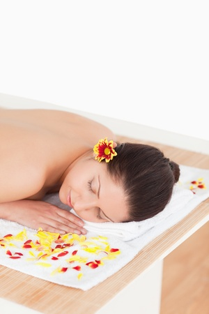 cute woman closing her eyes while surrounded by flowers in a spa photo