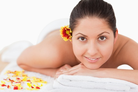 young beautiful woman having a flower on her ear while looking at the camera in a spa photo