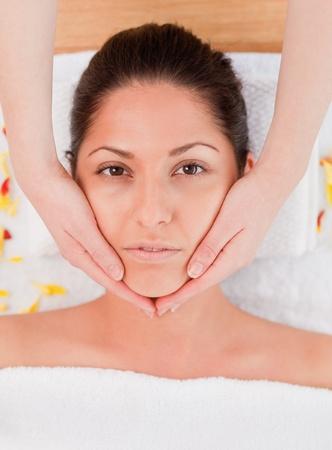 pretty woman having a facial massage looking at the camera photo