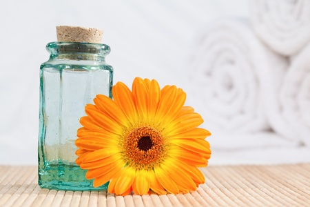 A glass phial and a sunflower with white towels on the background photo