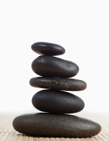 A black stones stack against a white background photo