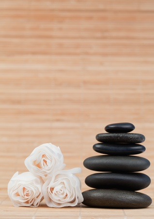 Roses and a black pebbles stack against a bamboo background photo